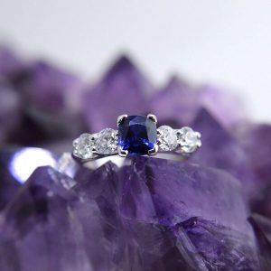 18k white gold ring with 1.13 carat blue sapphire and 4 round diamonds totaling 1 carat